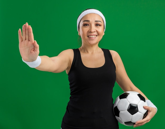 Jonge fitnessvrouw met hoofdband die voetbal vasthoudt met een glimlach op het gezicht en een stopgebaar maakt met open hand die over de groene muur staat