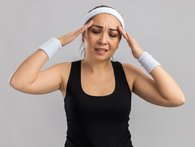 Jonge fitnessvrouw met hoofdband en armbanden die haar hoofd aanraakt en er onwel uitziet met hoofdpijn die over een witte muur staat