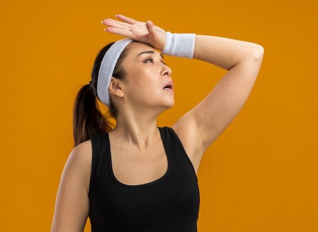 Jonge fitnessvrouw met hoofdband en armbanden die opkijkt met de hand op het hoofd die moe en overwerkt is en over een oranje muur staat