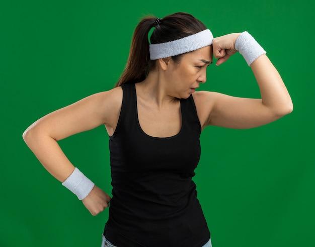 Jonge fitnessvrouw met hoofdband en armbanden die opzij kijkt met een peinzende uitdrukking die over een groene muur staat