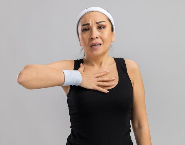 Jonge fitnessvrouw met hoofdband en armbanden die zich onwel voelen terwijl ze de hand op haar borst houdt terwijl ze over een witte muur staat