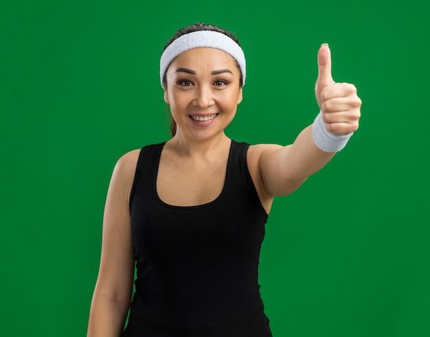 Jonge fitnessvrouw met hoofdband en armbanden met een glimlach op het gezicht met duimen die over een groene muur staan