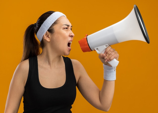 Jonge fitnessvrouw met hoofdband en armbanden schreeuwend naar megafoon met agressieve uitdrukking