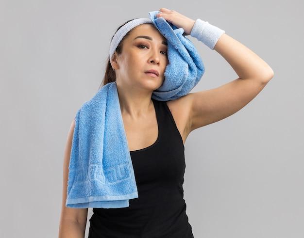 Jonge fitnessvrouw met hoofdband en handdoek om de nek die haar voorhoofd afveegt en er moe uitziet terwijl ze over een witte muur staat