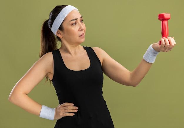 Jonge fitnessvrouw met hoofdband met halter die er verward naar kijkt en over groene muur staat