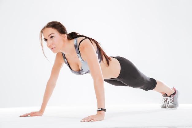 Jonge fitnessvrouw schudt pers in studio
