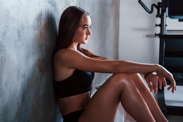 Jonge fitnessvrouw zit bij de muur met een fles water en neemt een pauze.