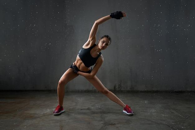 Jonge fitnesswoman die zich uitstrekt onder regen