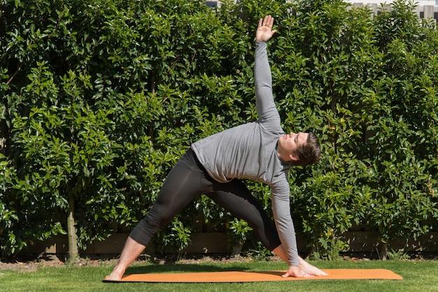Jonge fitte man die yoga beoefent en de driehoek doet poseren buitenshuis