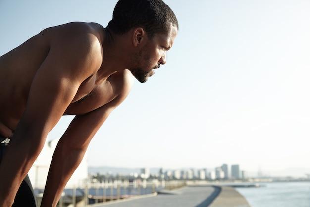 Jonge fitte man op het strand die het landschap bewondert