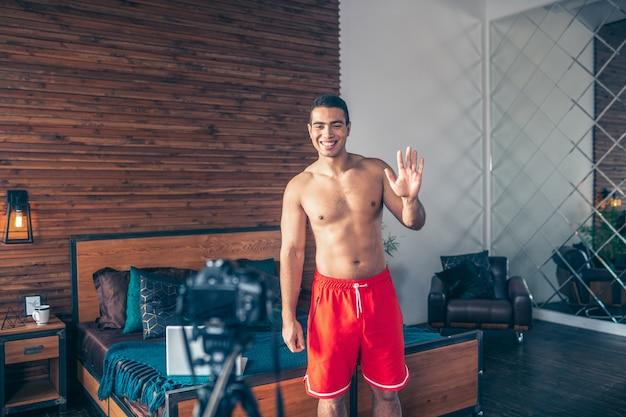 Jonge fitte sportieve vlogger in rode korte broek die zijn volgers begroet