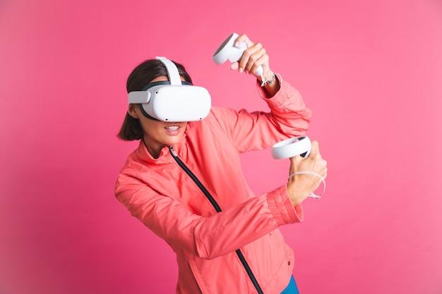 Jonge fitte vrouw in een sportjasje en een virtual reality-bril die boksgevechten speelt op roze