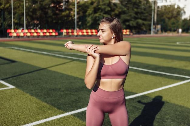 Jonge fitte vrouw in sportkleding die pre-training warming-up doet, hand die zich uitstrekt in het stadion. gezond levensstijlconcept. buitentraining