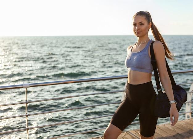 Jonge fitte vrouw in sportkleding met trainingstas kwam naar de ochtendtraining bij zonsopgang op het strand