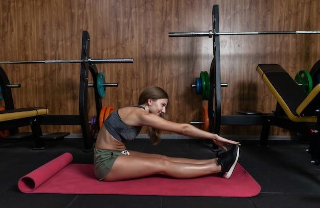 Jonge fitte vrouw in sportkleding oefent beenstrekken terwijl ze op de mat in de sportschool zit
