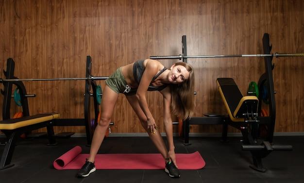 Jonge fitte vrouw in sportkleding oefent warming-up, strekt het lichaam uit in de sportschool