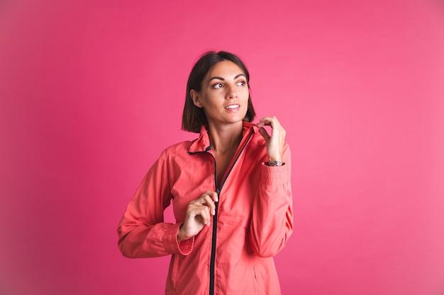 Jonge fitte vrouw in sportkledingjasje op roze