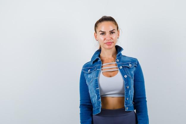 Jonge fitte vrouw in top, spijkerjasje en verbijsterd op zoek. vooraanzicht.