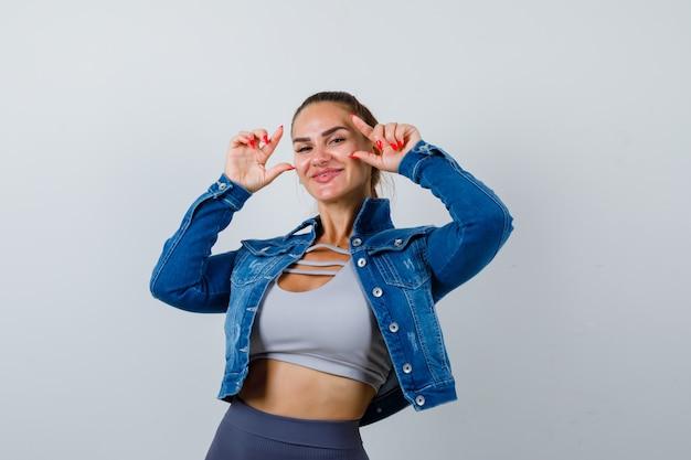 Jonge fitte vrouw met maatbord in top, spijkerjasje en vrolijk, vooraanzicht.