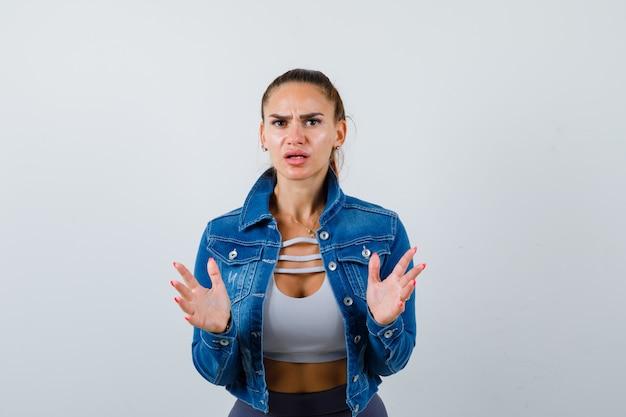 Jonge fitte vrouw toont overgavegebaar in top, spijkerjasje en kijkt verbijsterd. vooraanzicht.