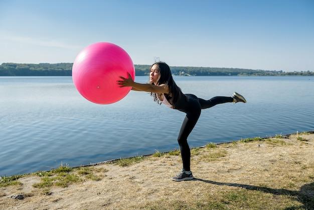 Jonge flexibele vrouw die ochtendgeschiktheidsoefeningen op roze bal dichtbij meer doet
