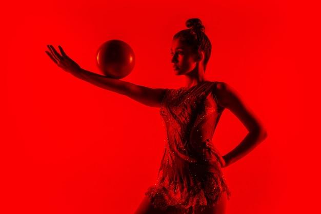 Jonge flexibele vrouwelijke turnster die op rood wordt geïsoleerd