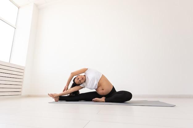 Jonge flexibele zwangere vrouw die gymnastiek op tapijt op de vloer op witte achtergrond doet het concept