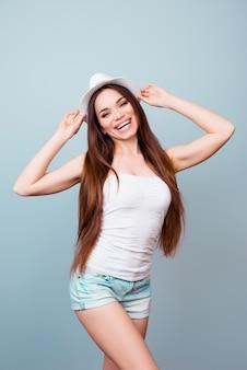 Jonge flirterige brunette dame in zomer outfit en hoed staat in verleidelijke pose op een lichtblauwe ruimte. ze is zo mager en aantrekkelijk, heeft lang mooi haar, stralende glimlach