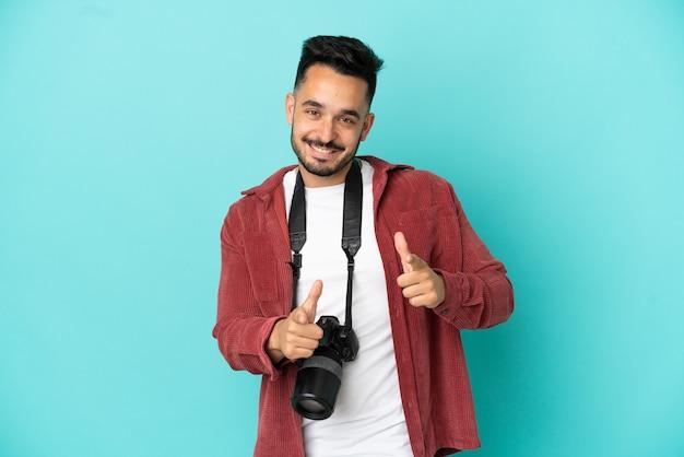 Jonge fotograaf blanke man geïsoleerd op een blauwe achtergrond die naar voren wijst en glimlacht