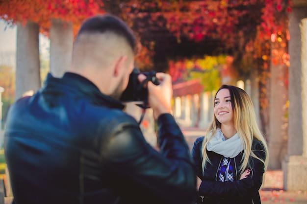 Jonge fotograaf die een foto van een mooi meisje in een park maakt