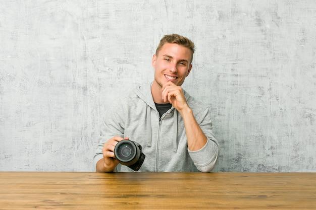 Jonge fotograaf die een fotocamera op een lijst houden die gelukkig en zeker glimlachen, wat betreft kin met hand.