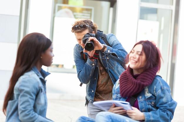 Jonge fotograaf die foto's van twee meisjes neemt terwijl het bestuderen.