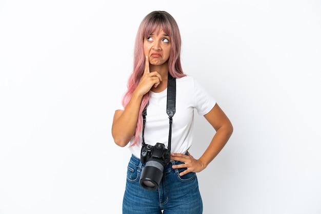 Jonge fotograaf gemengd ras vrouw met roze haren geïsoleerd op een witte achtergrond met twijfels tijdens het opzoeken