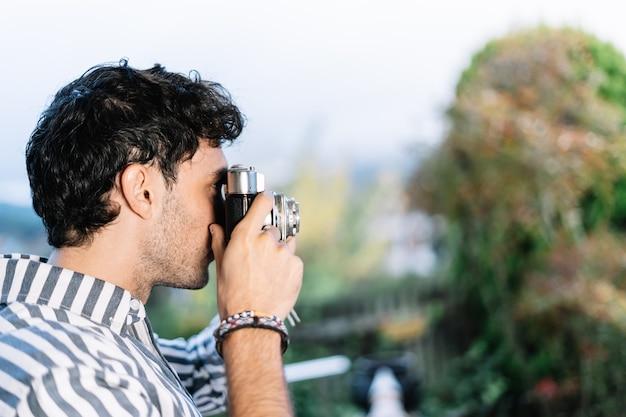 Jonge fotograaf maakt een foto met een retro camera