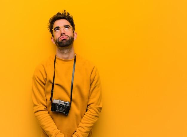 Jonge fotograaf man moe en verveeld