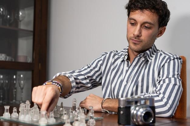 Jonge fotograaf speelt een spelletje schaak met een camera naast hem