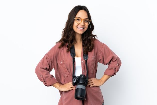 Jonge fotograaf vrouw over geïsoleerde witte achtergrond poseren met armen op heup en glimlachen
