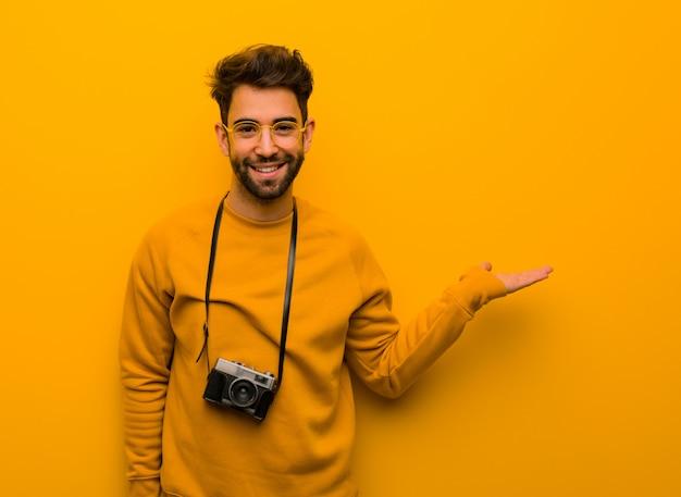Jonge fotograafmens die iets met hand houdt