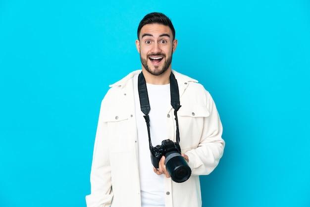 Jonge fotograafmens die op blauwe muur met verrassingsgelaatsuitdrukking wordt geïsoleerd