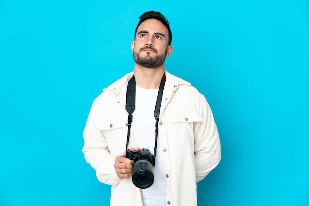 Jonge fotograafmens die op blauwe muur wordt geïsoleerd en omhoog wordt gekeken