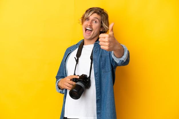Jonge fotograafmens die op gele muur met omhoog duimen wordt geïsoleerd omdat er iets goeds is gebeurd