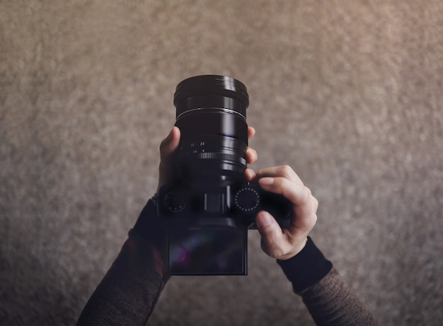 Jonge fotograafvrouw die camera gebruiken om foto te nemen. donkere tint, pov of bovenaanzicht in lage hoek. selectieve focus op lcd-scherm