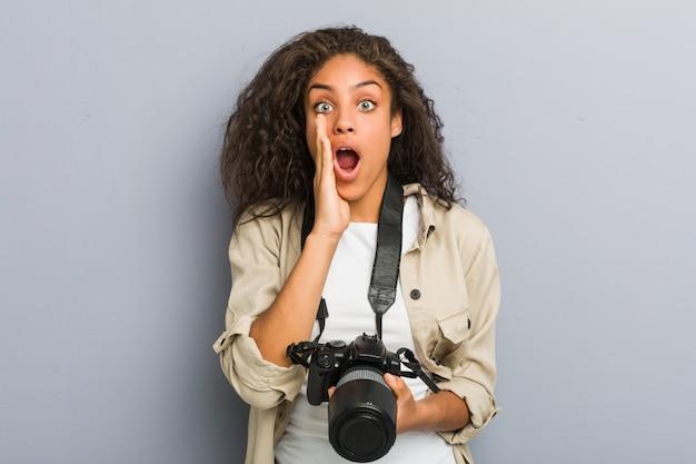 Jonge fotograafvrouw die camera schreeuwen opgewekt houden aan voorzijde uit