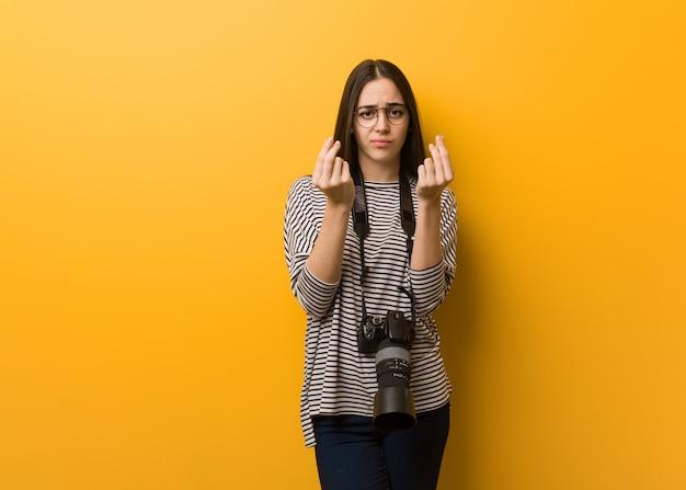 Jonge fotograafvrouw die een gebaar van behoefte doet