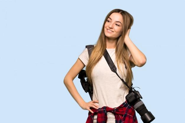 Jonge fotograafvrouw die een idee denken terwijl het krassen van hoofd op blauwe muur