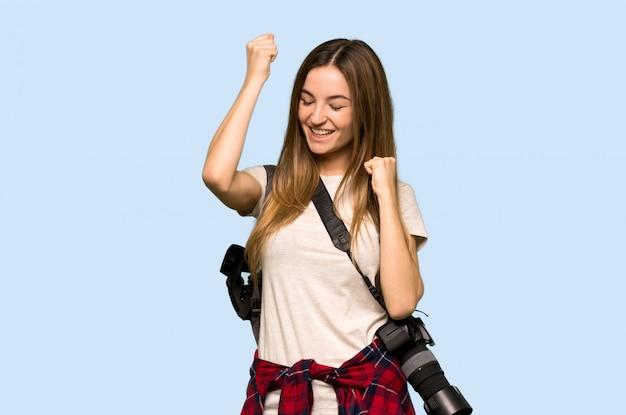 Jonge fotograafvrouw die een overwinning op blauwe muur viert