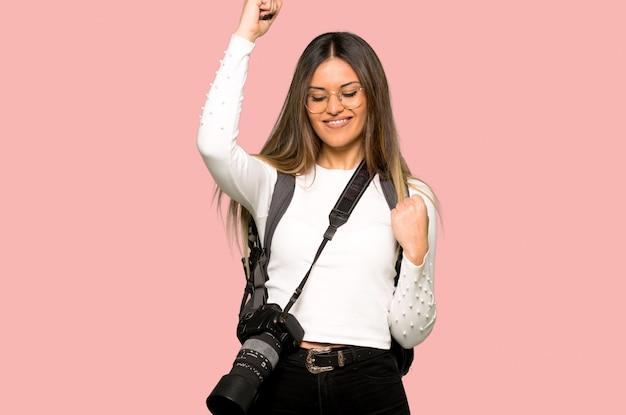 Jonge fotograafvrouw die een overwinning op geïsoleerde roze muur viert