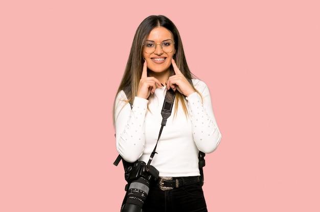 Jonge fotograafvrouw die met een gelukkige en prettige uitdrukking op geïsoleerde roze muur glimlachen