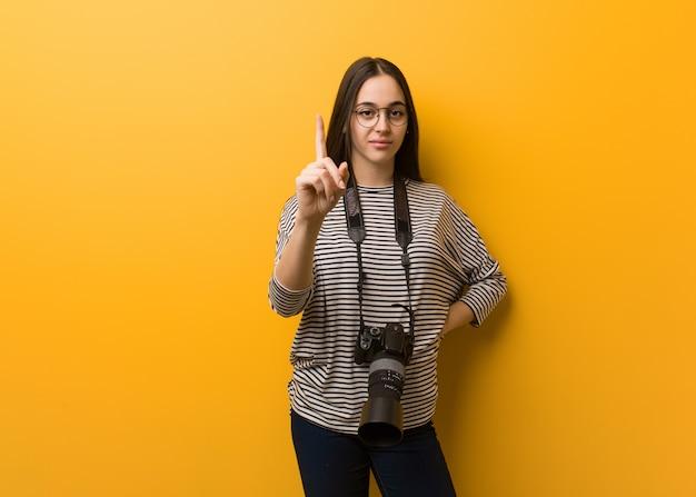 Jonge fotograafvrouw die nummer één toont