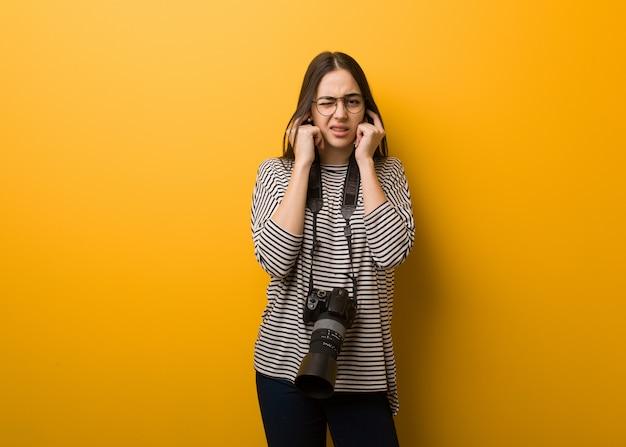 Jonge fotograafvrouw die oren behandelen met handen